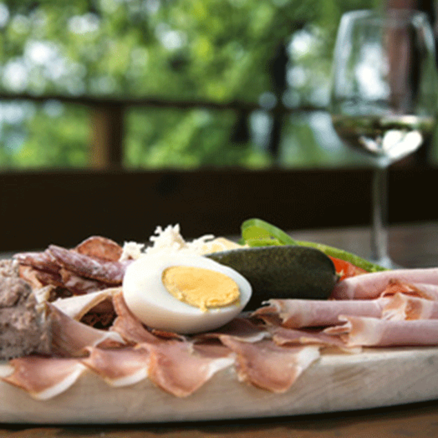 Covered chef's board with ham, eggs, horseradish and, of course, a South Styrian wine