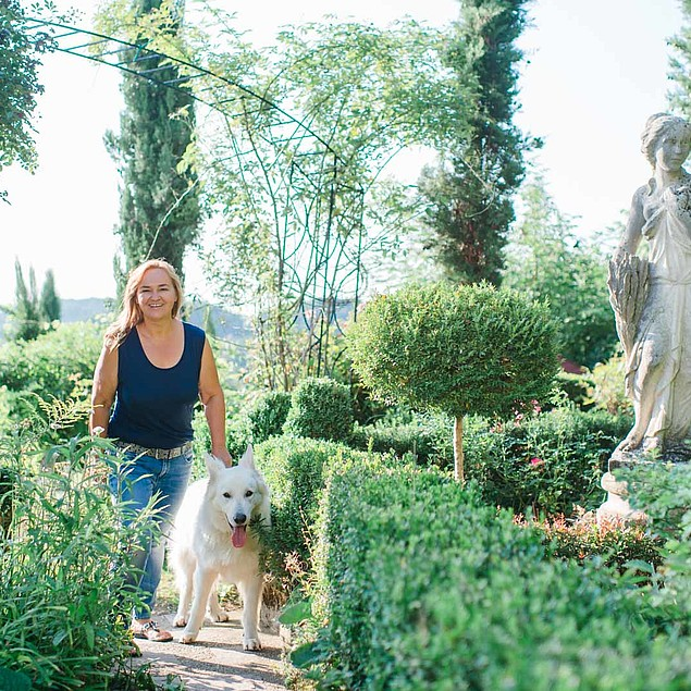 Renate Polz with her white dog in her romantic garden